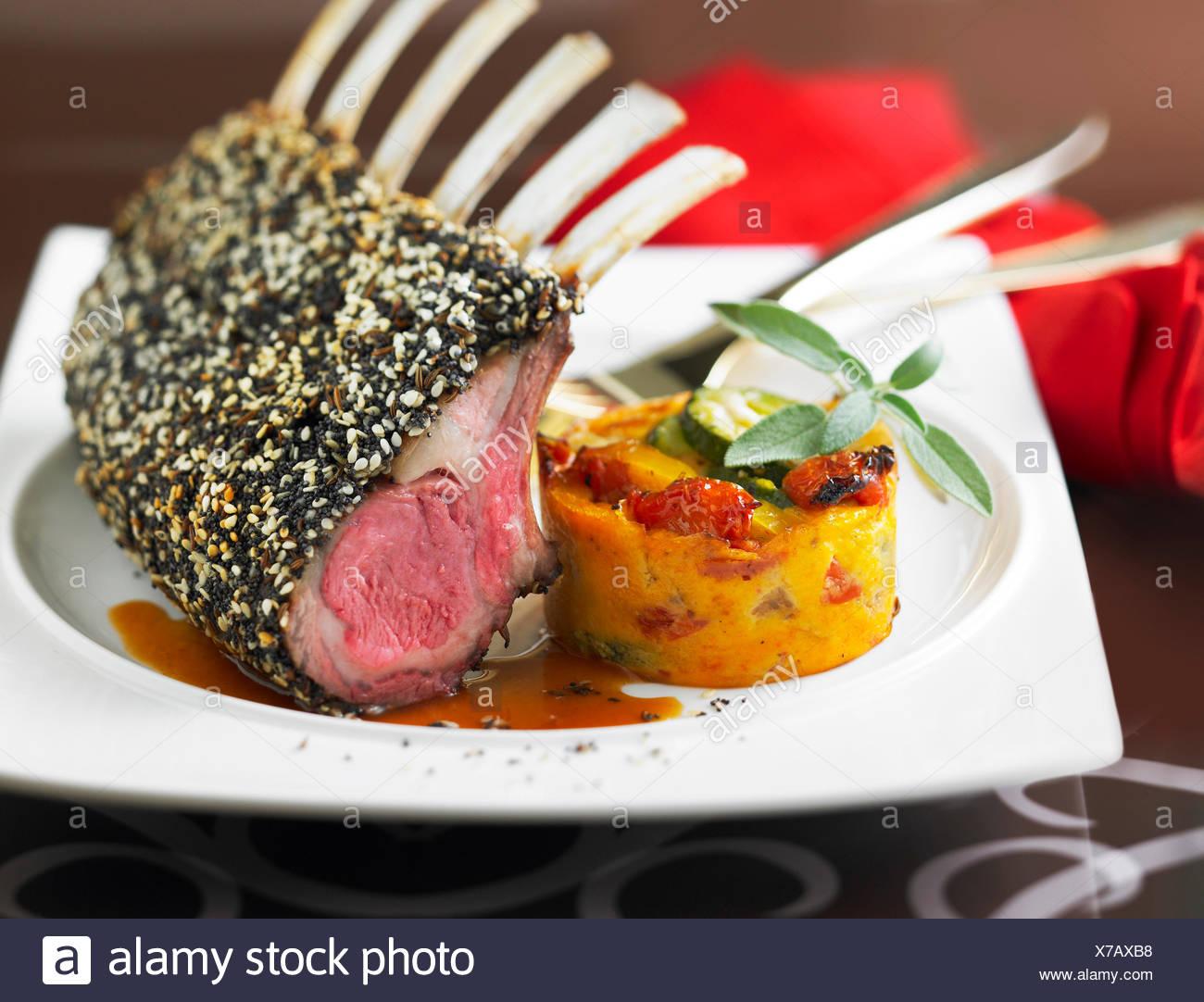 Loin of lamb in a seedy crust ,mini vegetable flan - Stock Image