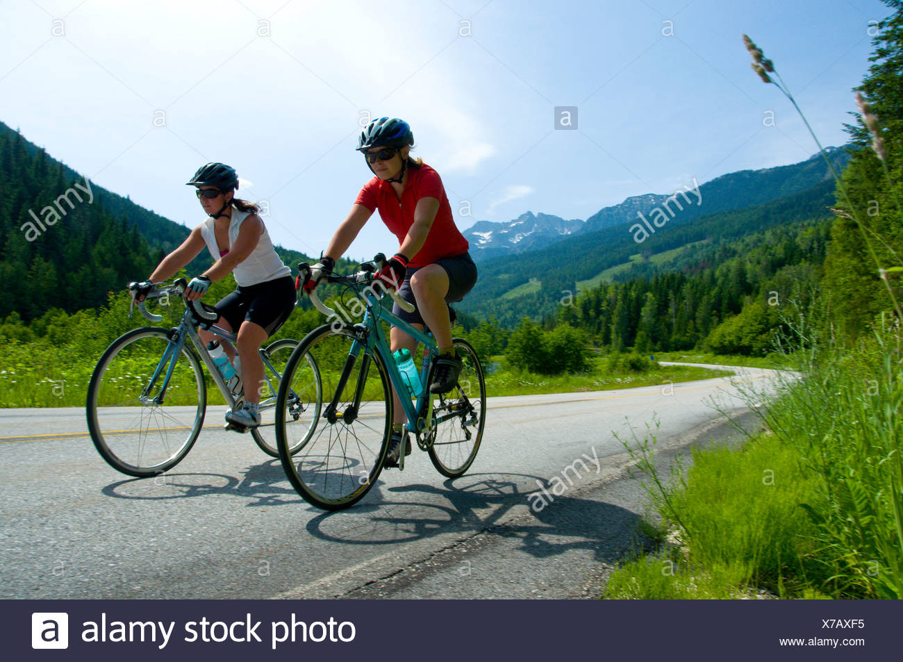 Two young women cycling on their road bikes take the scenic route from Kaslo to New Denver, British Columbia, Canada - Stock Image