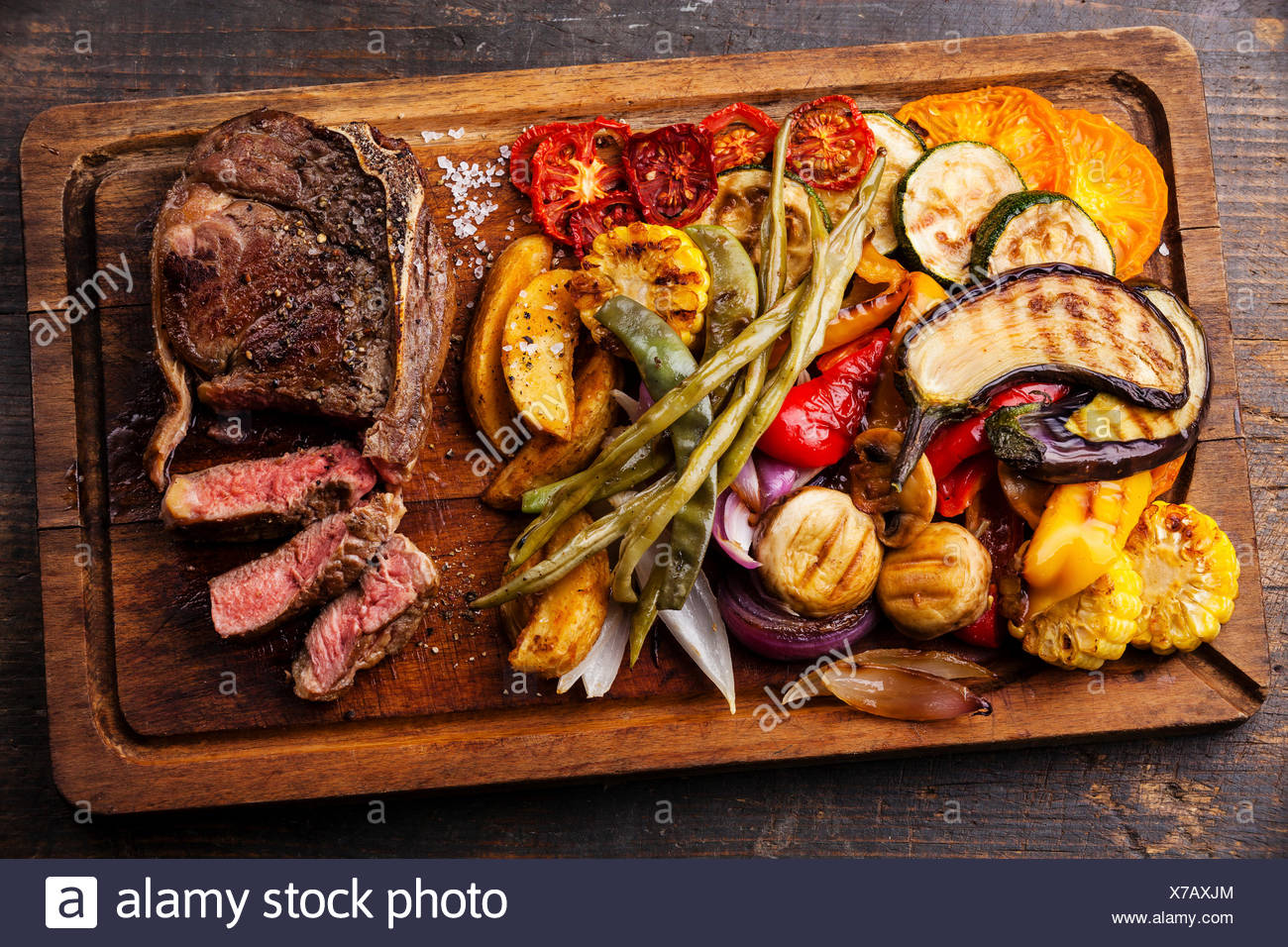 Club Beef steak with pepper sauce and Grilled vegetables on cutting board on dark wooden background - Stock Image