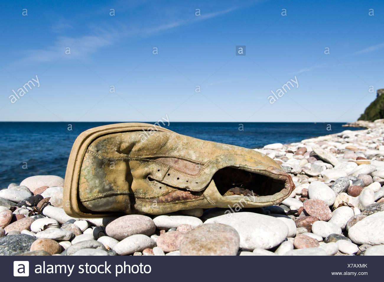 Old damaged shoe on stone beach - Stock Image