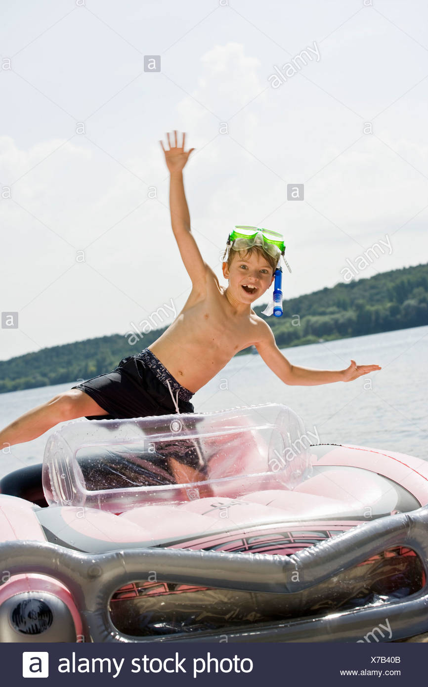 A young boy standing in an inflatable raft on a lake Stock Photo