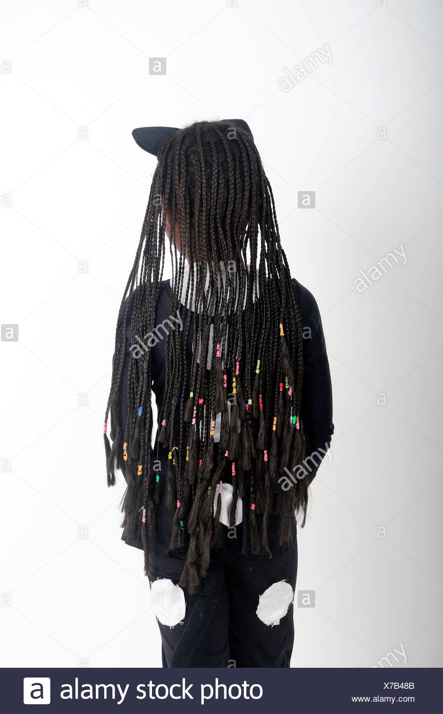 Young African girl with braided and beaded hair as seen from her back - Stock Image