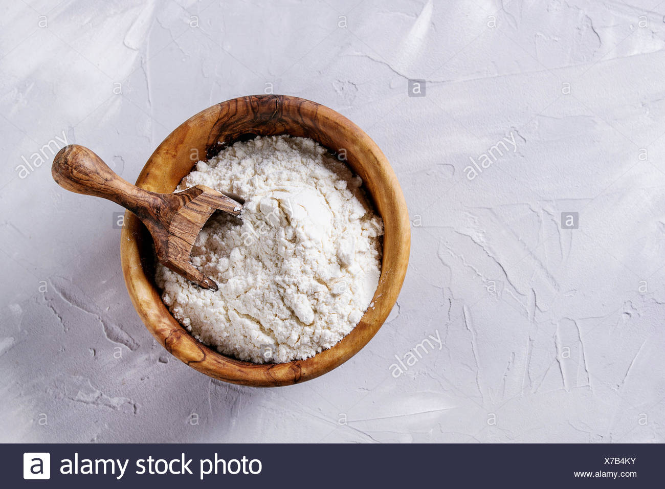 Olive wood bowl with wheat flour and scoop for home baking. Over gray concrete background. Top view, copy space - Stock Image