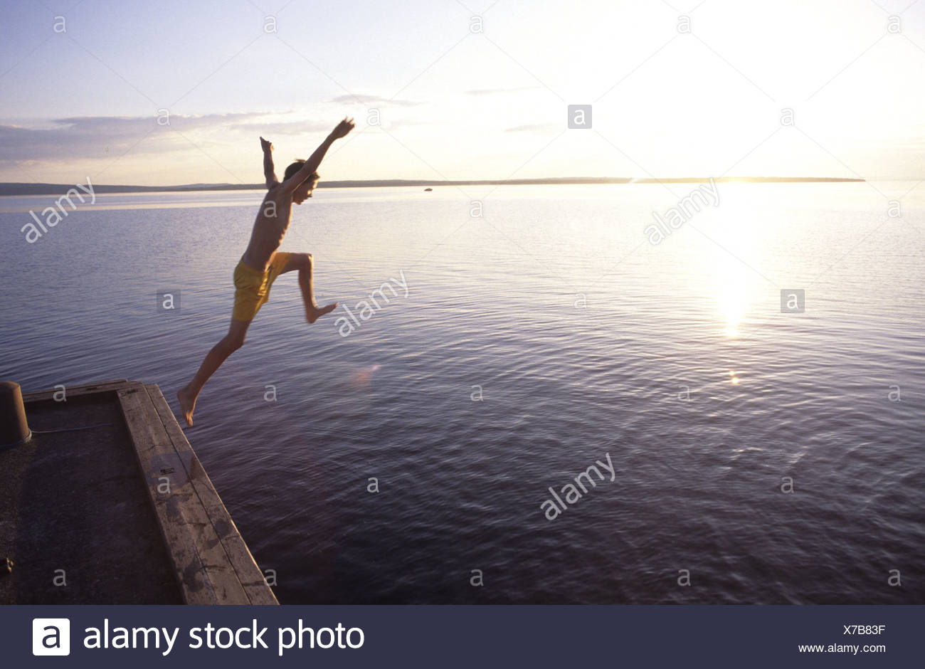Boy jumping from at jetty - Stock Image