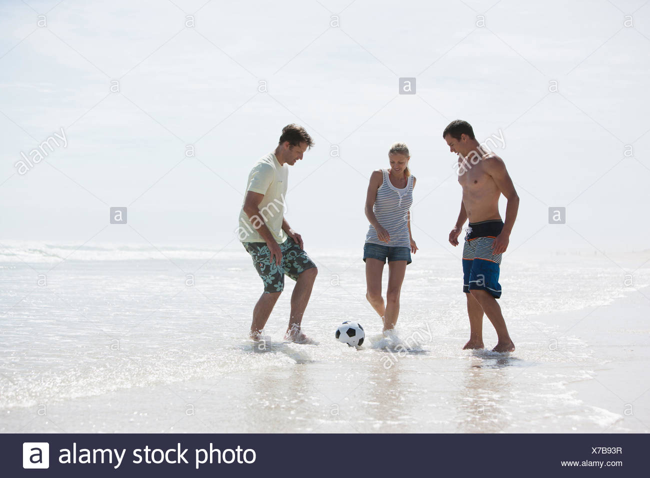 Friends playing football on beach Stock Photo