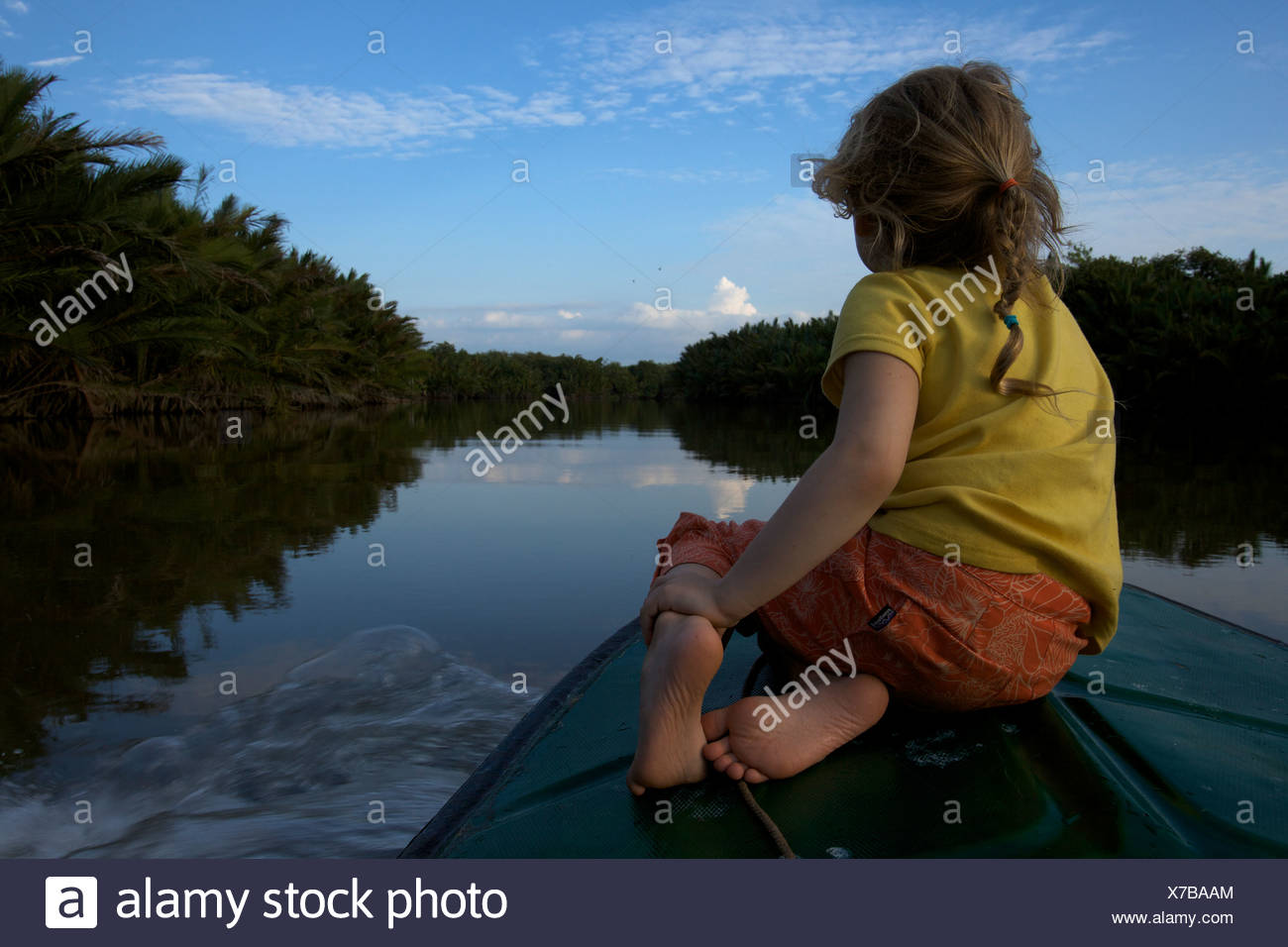 A girl rides on the bow of a boat on a river in Borneo. - Stock Image