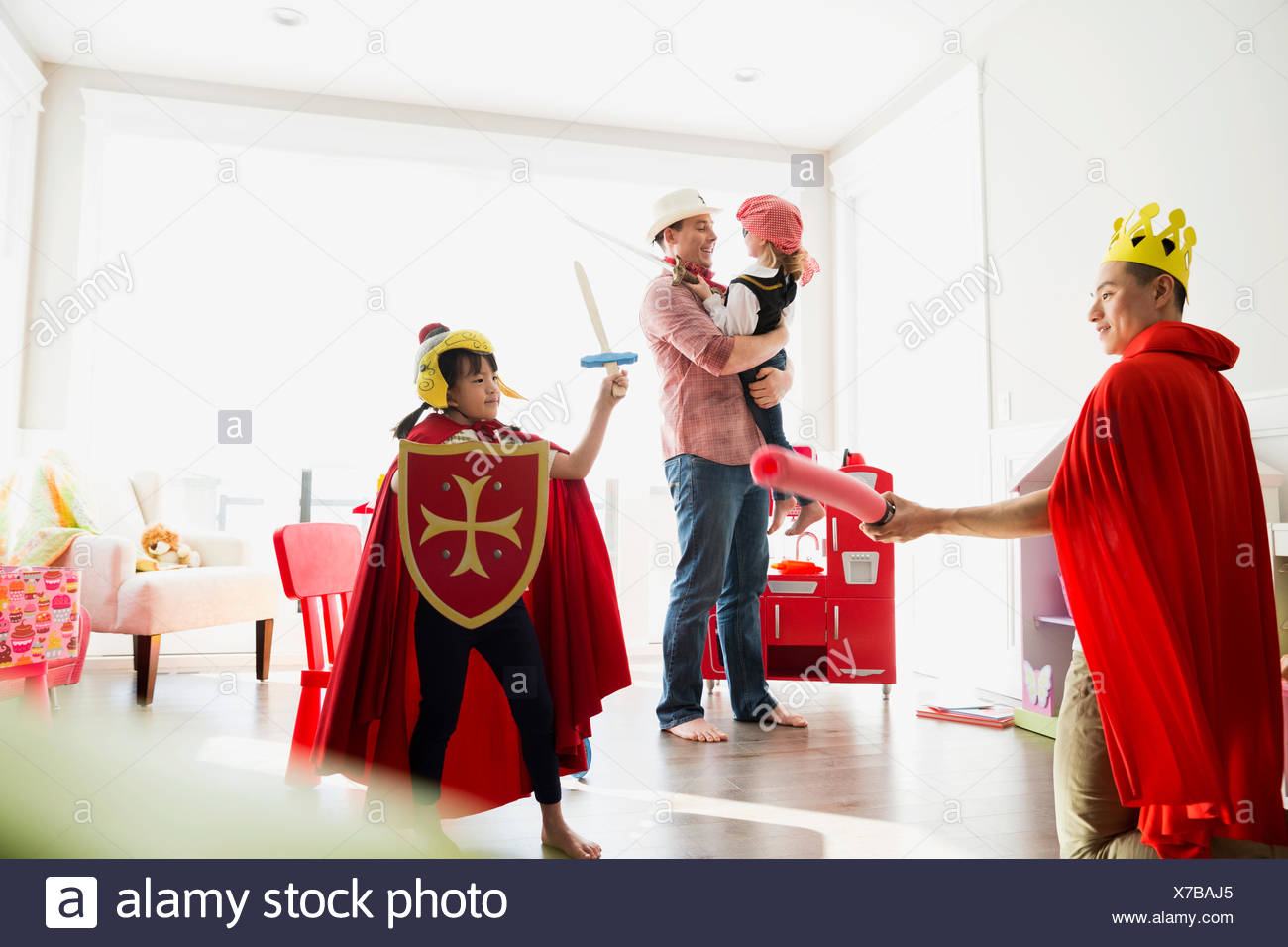 Father and daughter in costumes playing sword fight Stock Photo