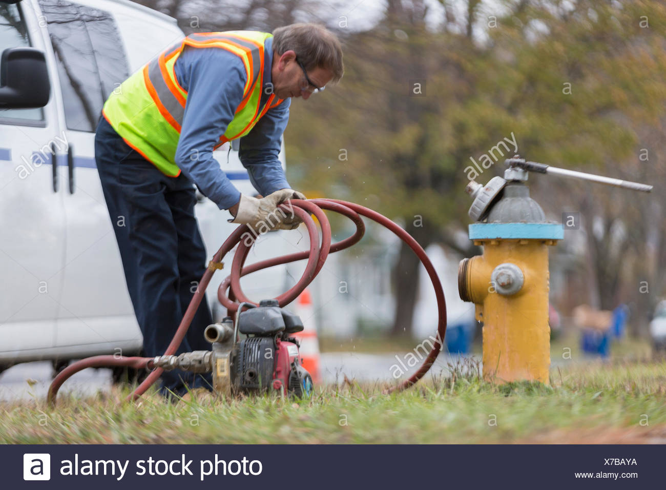 Water department technician coiling hose used to flush hydrant - Stock Image