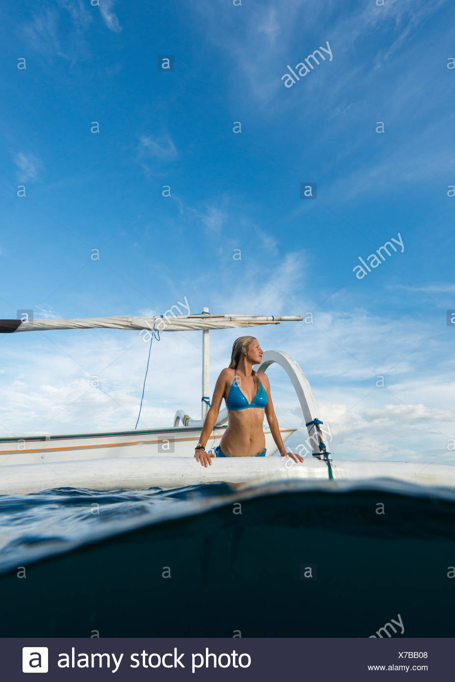 Woman getting out of the sea onto a boat, Bali, Indonesia Stock Photo
