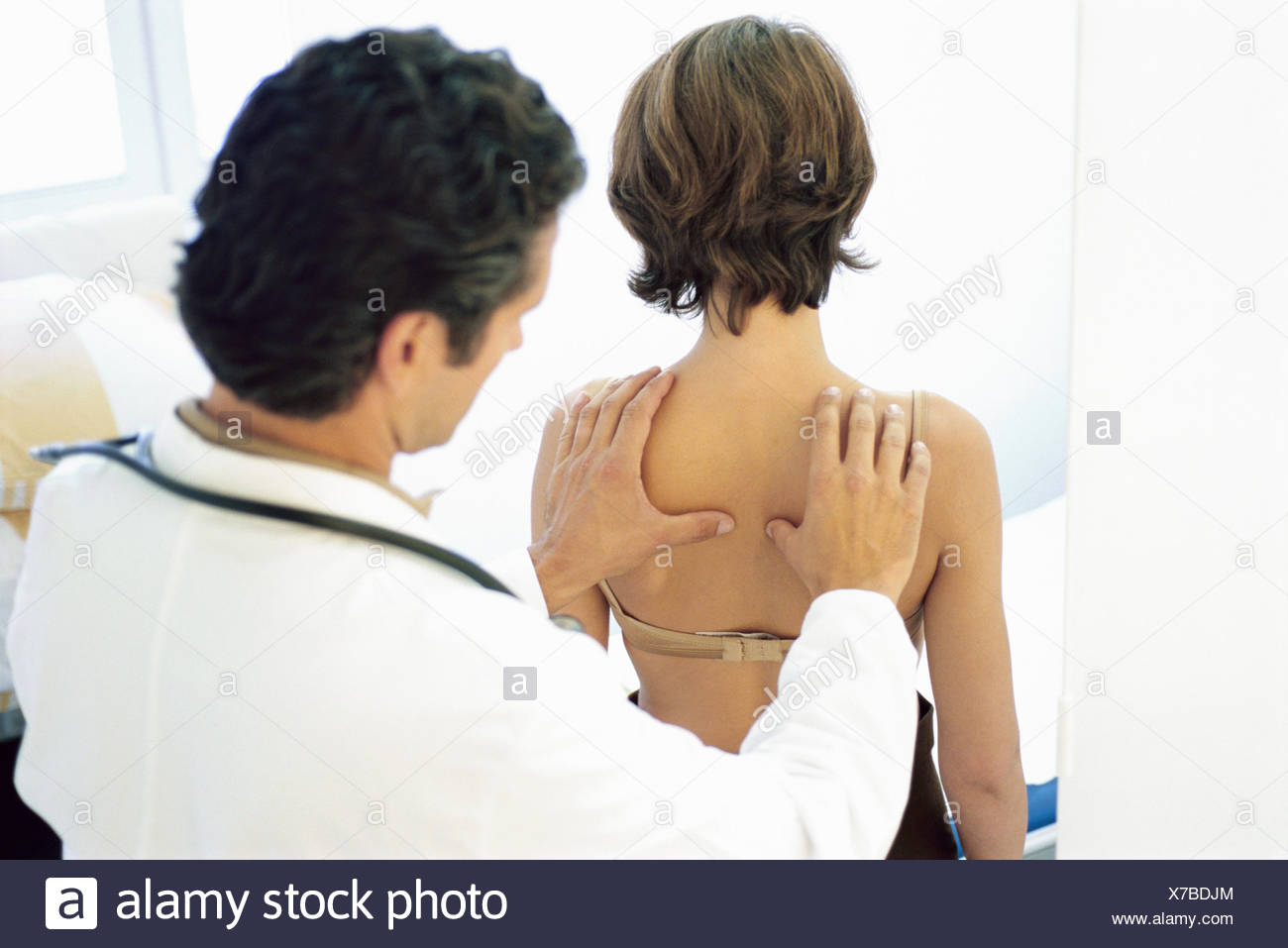 View of a male doctor checking a young woman's lungs - Stock Image