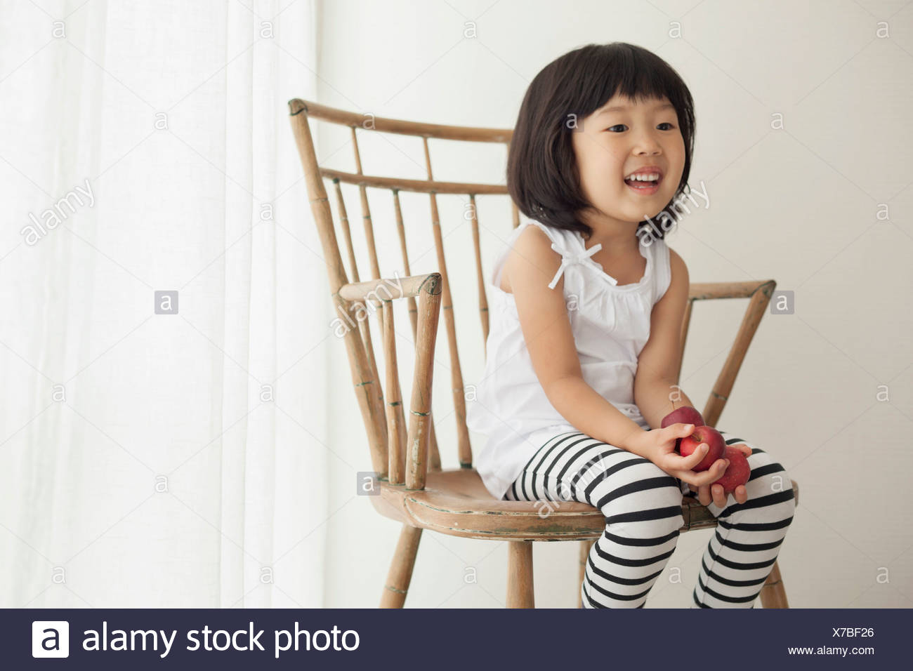 Girl sitting on wooden chair, portrait - Stock Image