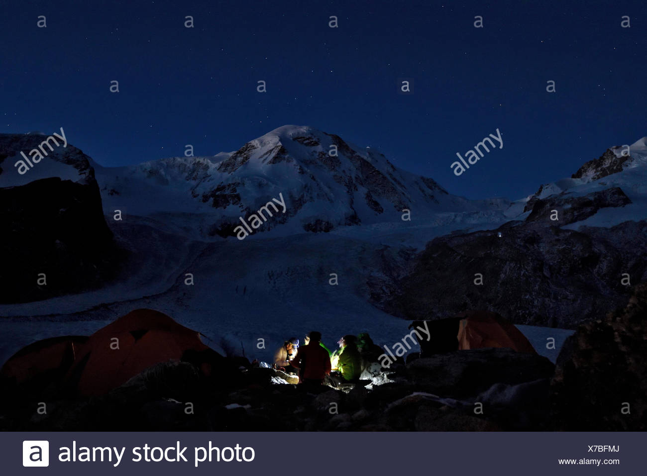 Four Italian cave explorers enjoy their last night on the glacier beneath the stars eating their meal. The faint outline and shape of the Gornergletsc - Stock Image