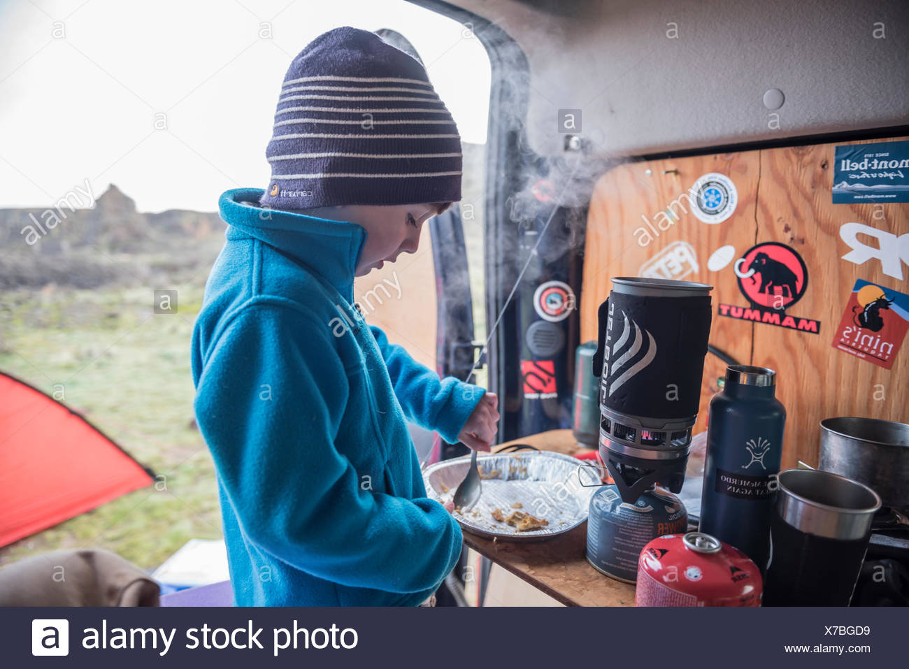 A young boy finishes the last few crumbs of pie crust during a camping trip. - Stock Image