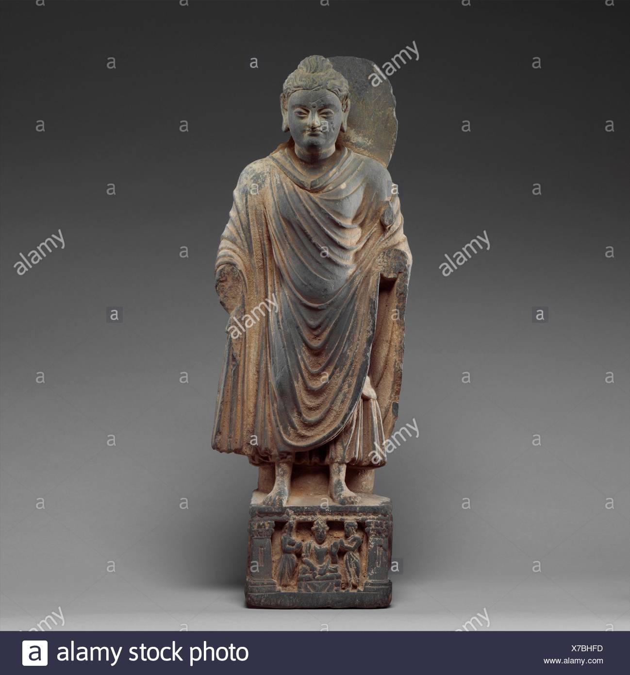 Standing Buddha. Date: ca. 3rd-4th century; Culture: Pakistan (ancient region of Gandhara); Medium: Schist; Dimensions: H. 20 in. (50.8 cm); W. 7 1/4 Stock Photo