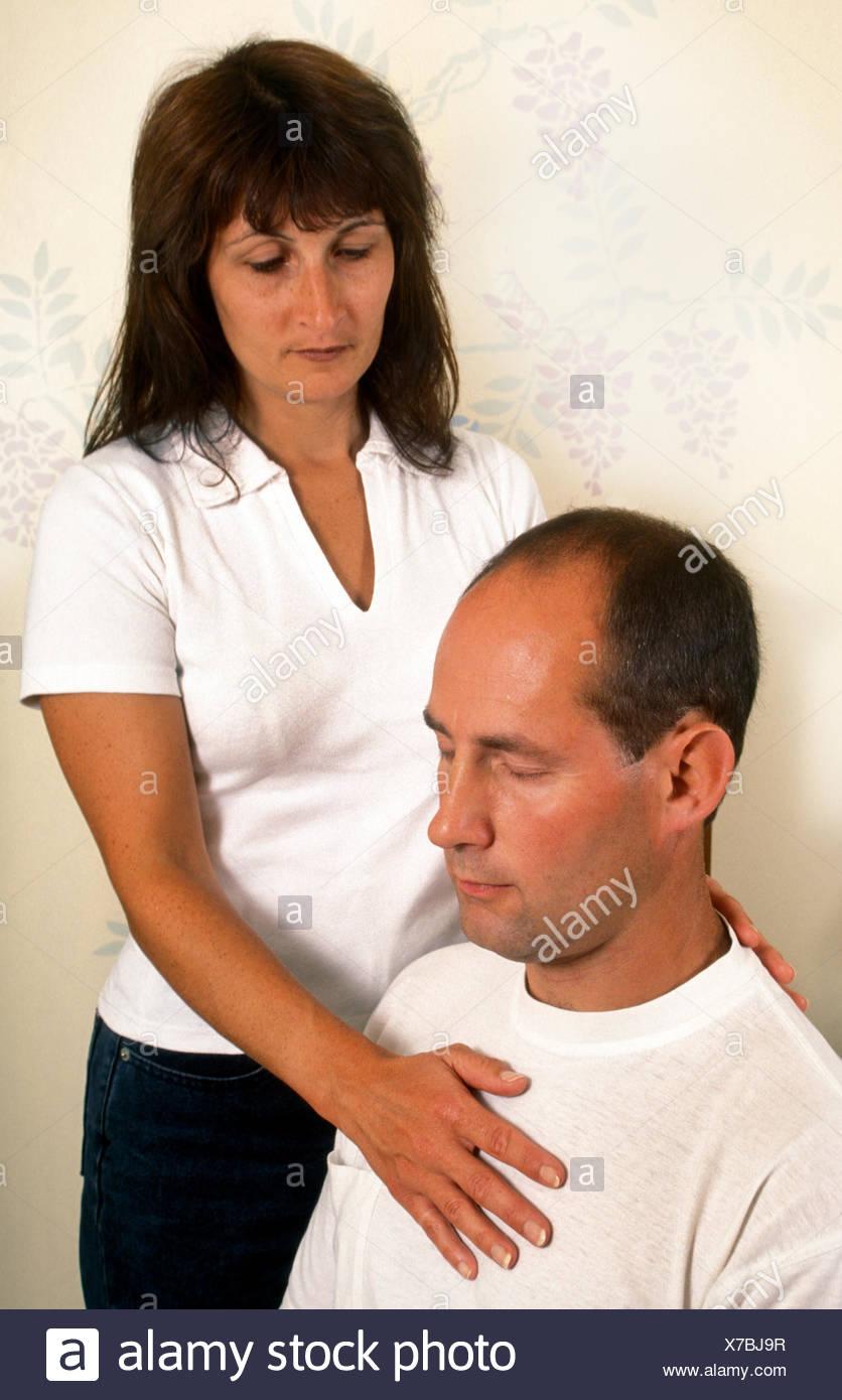 Woman giving hands on Reiki or spiritual healing to man - Stock Image