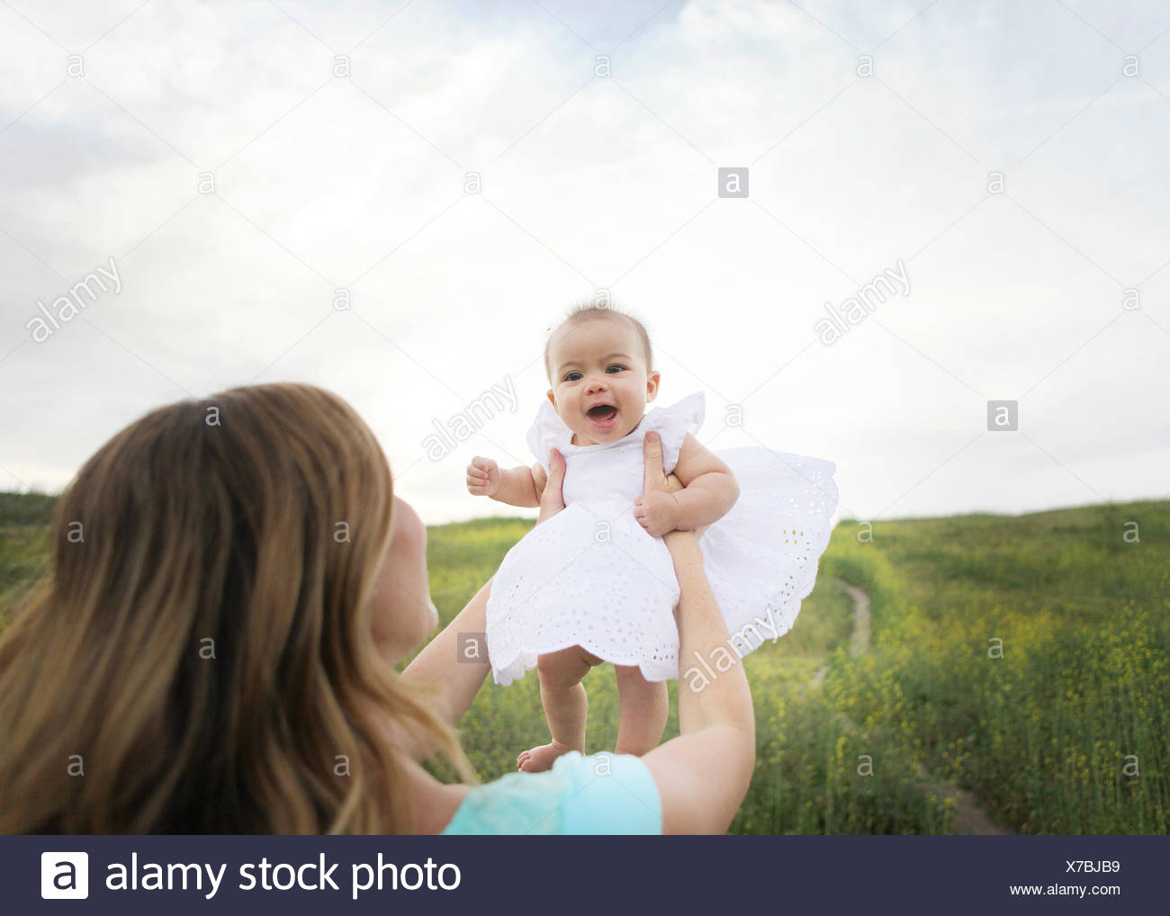 Mother lifting baby girl in the air - Stock Image