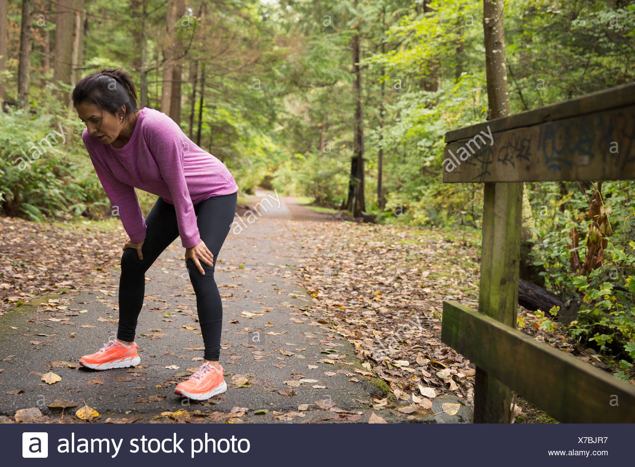 Tired woman resting hands knees after run woods - Stock Image