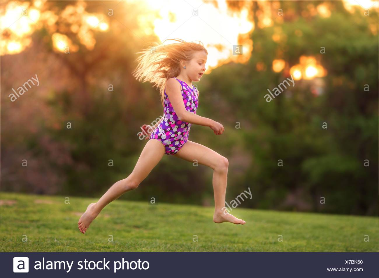 USA, Little girl (8-9) wearing swimsuit jumping in back yard - Stock Image