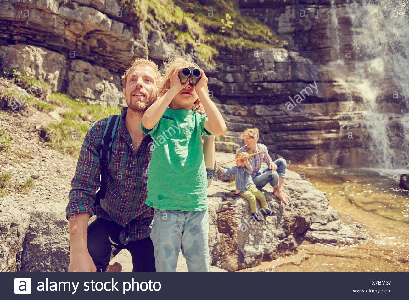 Young family exploring beside waterfall - Stock Image