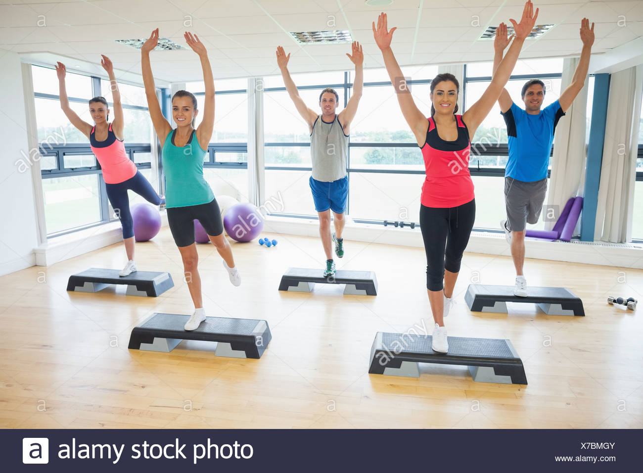 Instructor with fitness class performing step aerobics exercise - Stock Image