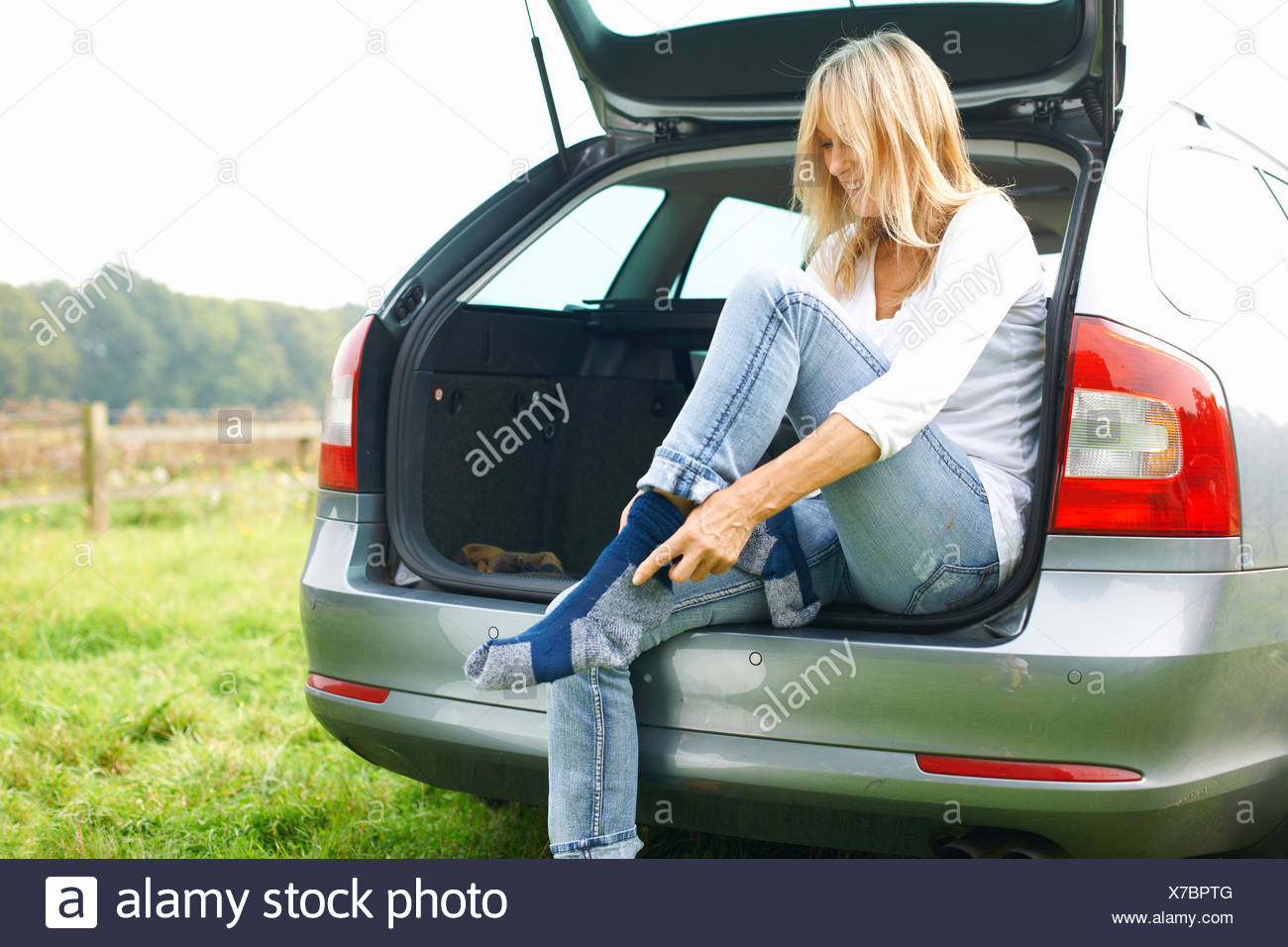 Woman sitting at rear of car putting on socks - Stock Image