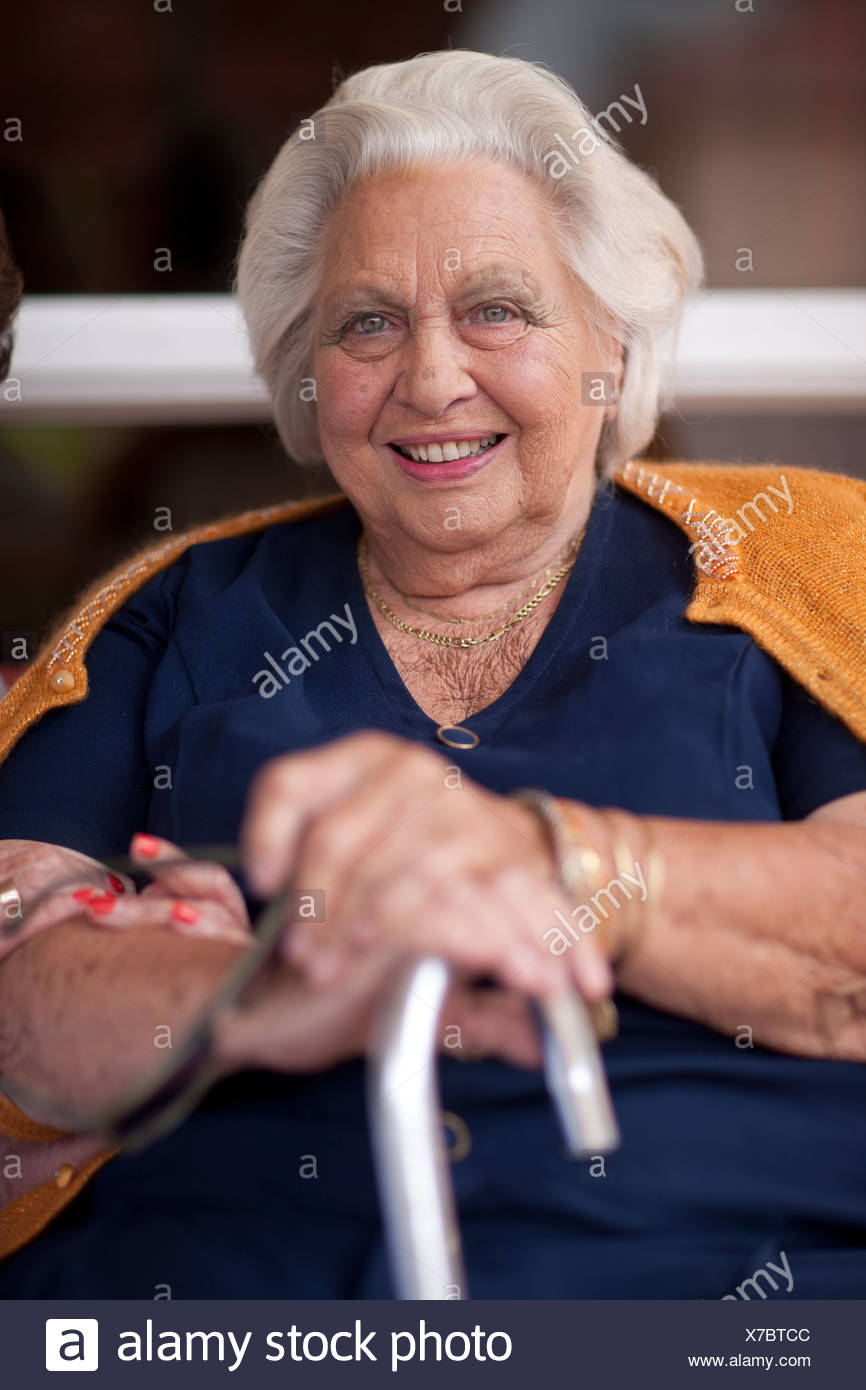 Portrait of happy senior woman holding walking stick Stock Photo