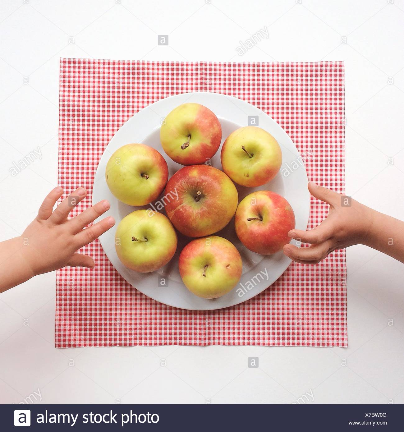 Two boys reaching for apples - Stock Image