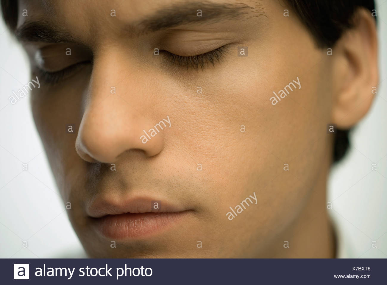 Young man furrowing brow, eyes closed, portrait - Stock Image
