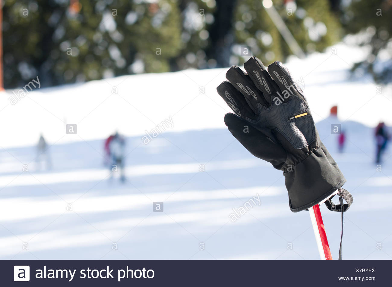 Ski gloves and sticks. Winter tourists on the background - Stock Image