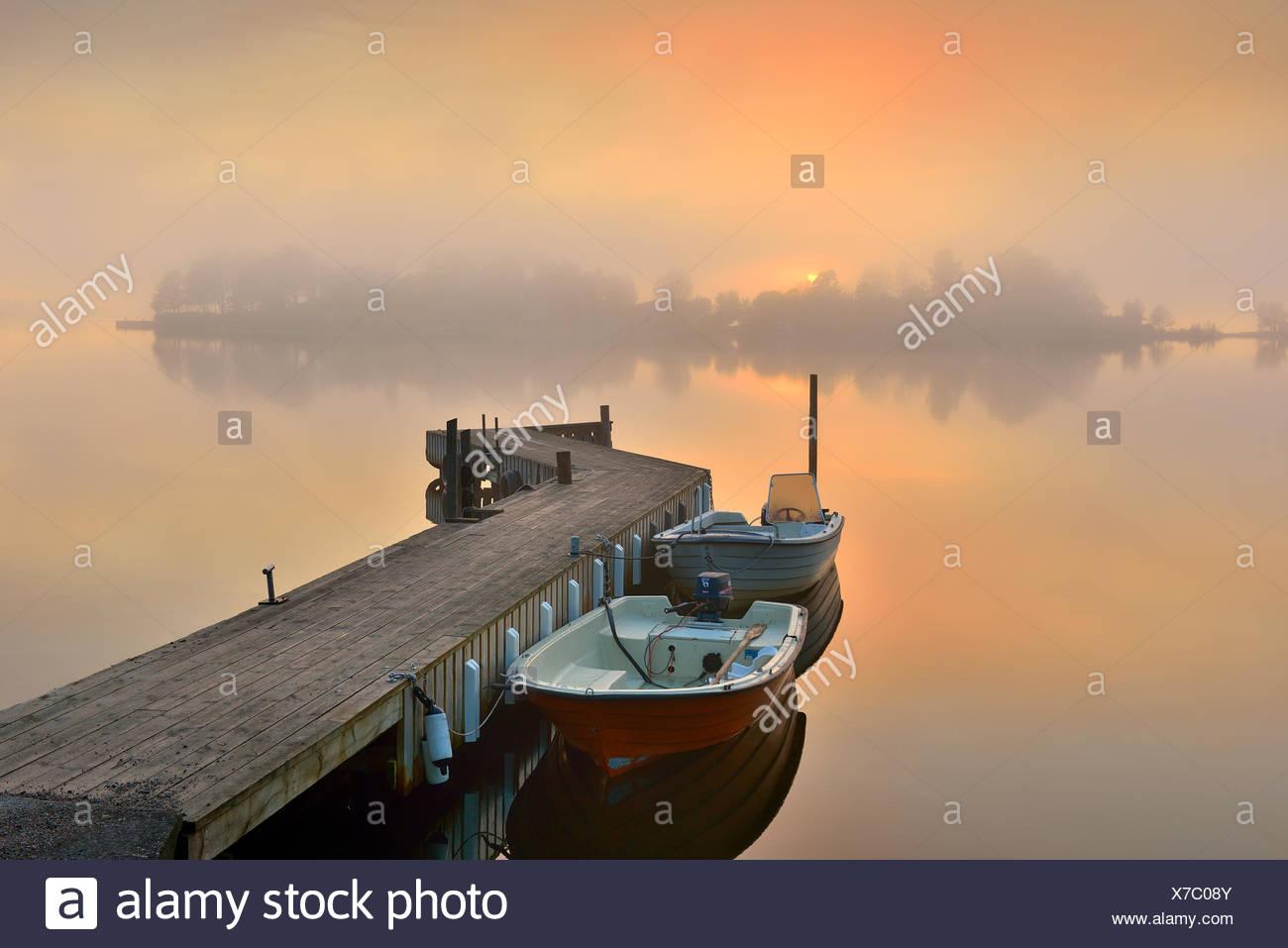 Sweden, Stockholm Archipelago, Uppland, Lidingo, Jetty and anchored boat at foggy dawn - Stock Image