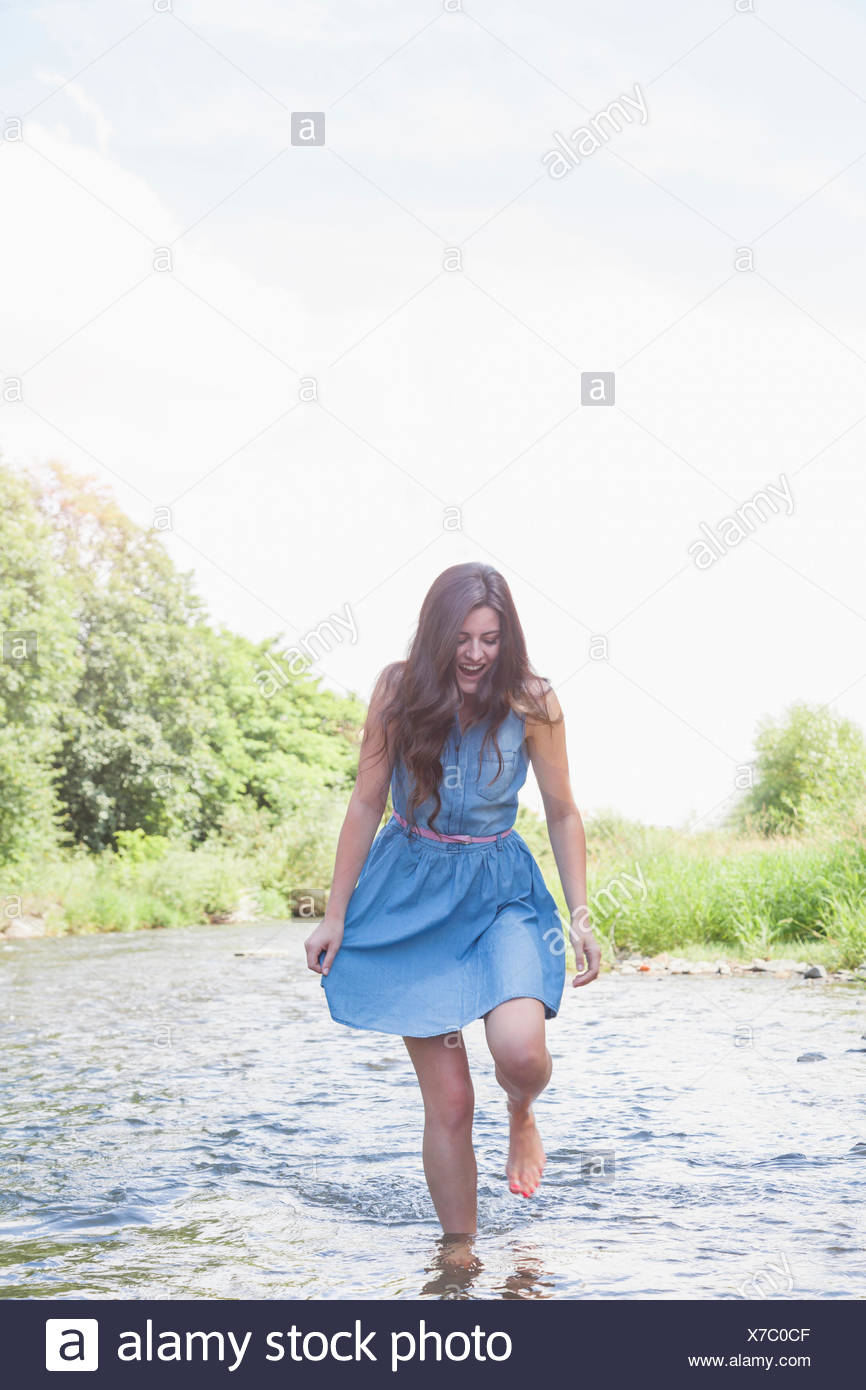 Young woman in shallow stream - Stock Image