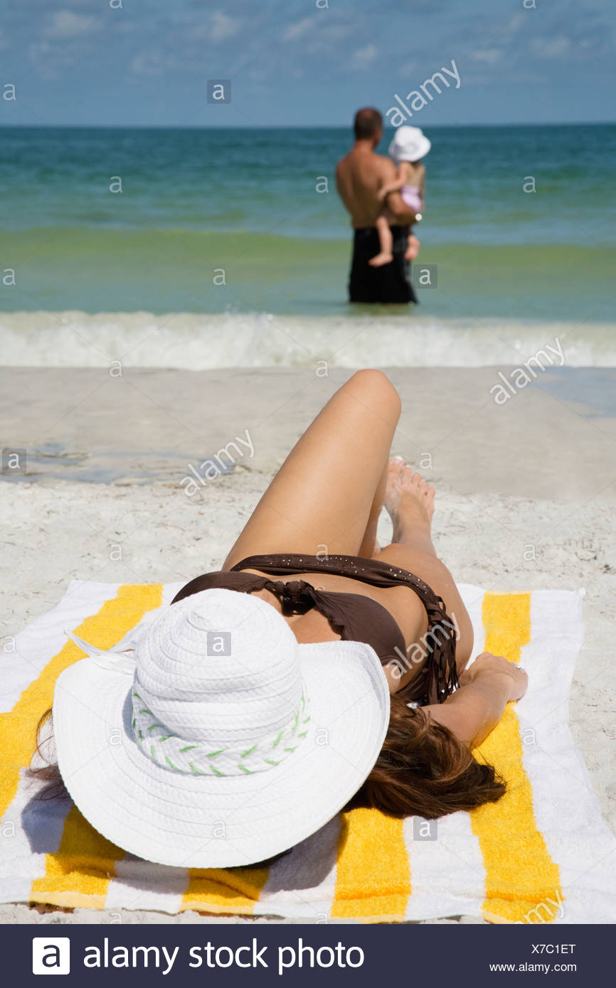 Woman sunbathing on beach, husband with child standing in ocean - Stock Image