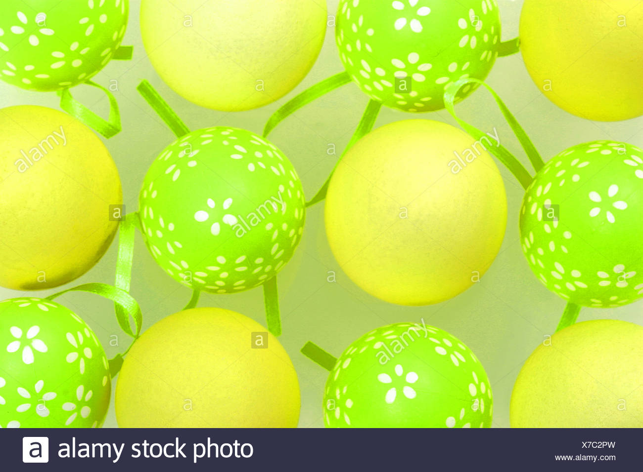Eggs painted green eggs white flower pattern, arranged alternately pale yellow eggs green ribbons inbetween them - Stock Image