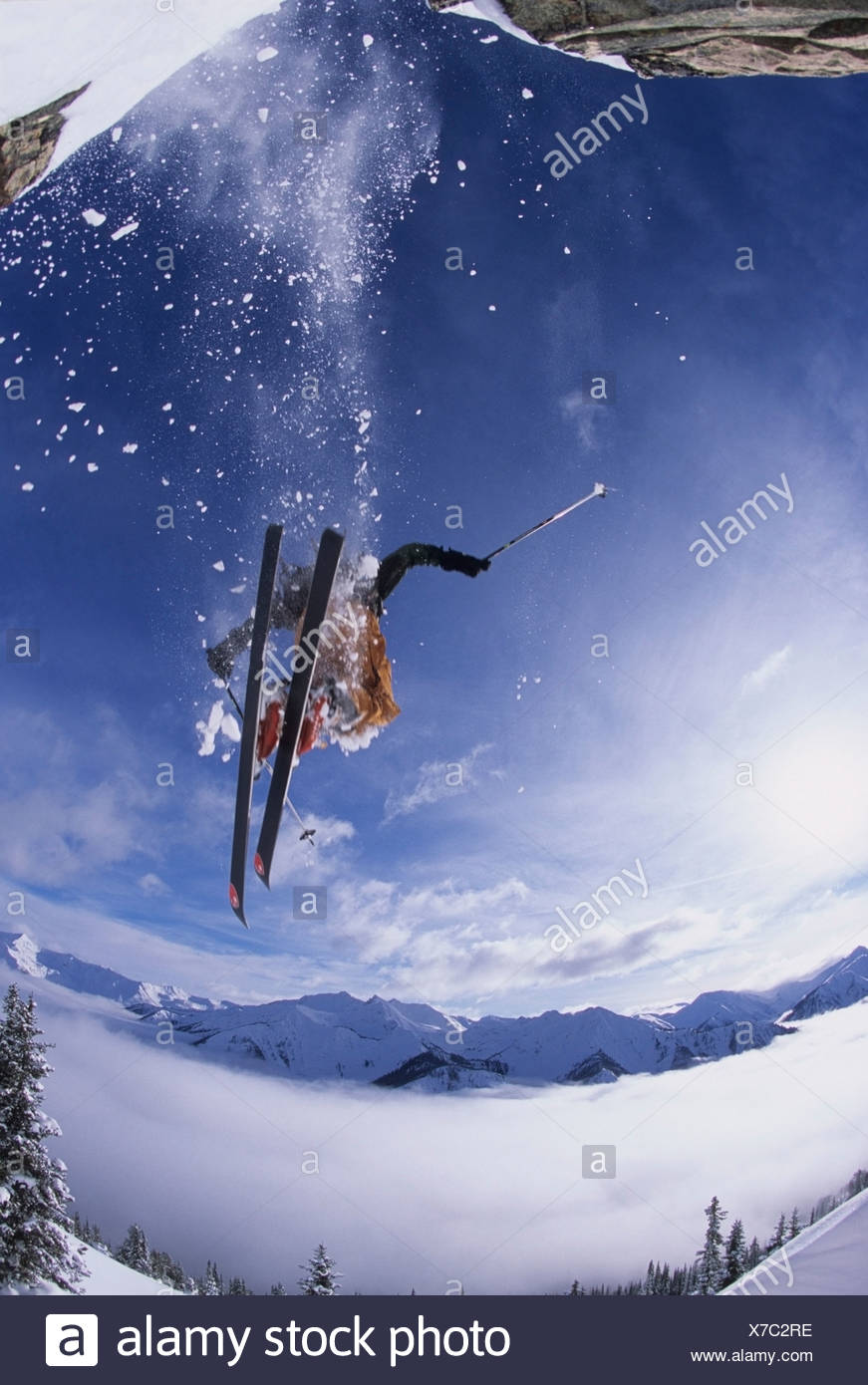 A skier catching some air after jumping a cliff in the backcountry of Kickinghorse Resort Area, Golden, British Columbia, Canada - Stock Image