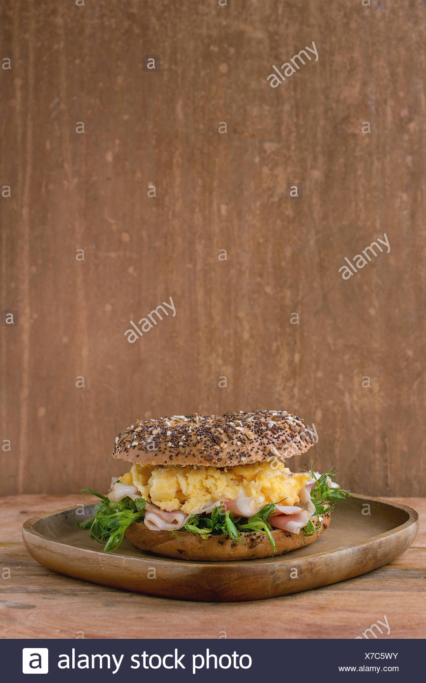 Sprinkle seeds Whole Grain bagels with scrambled eggs, pea sprout and prosciutto ham on wood plate over wooden textured backgrou - Stock Image