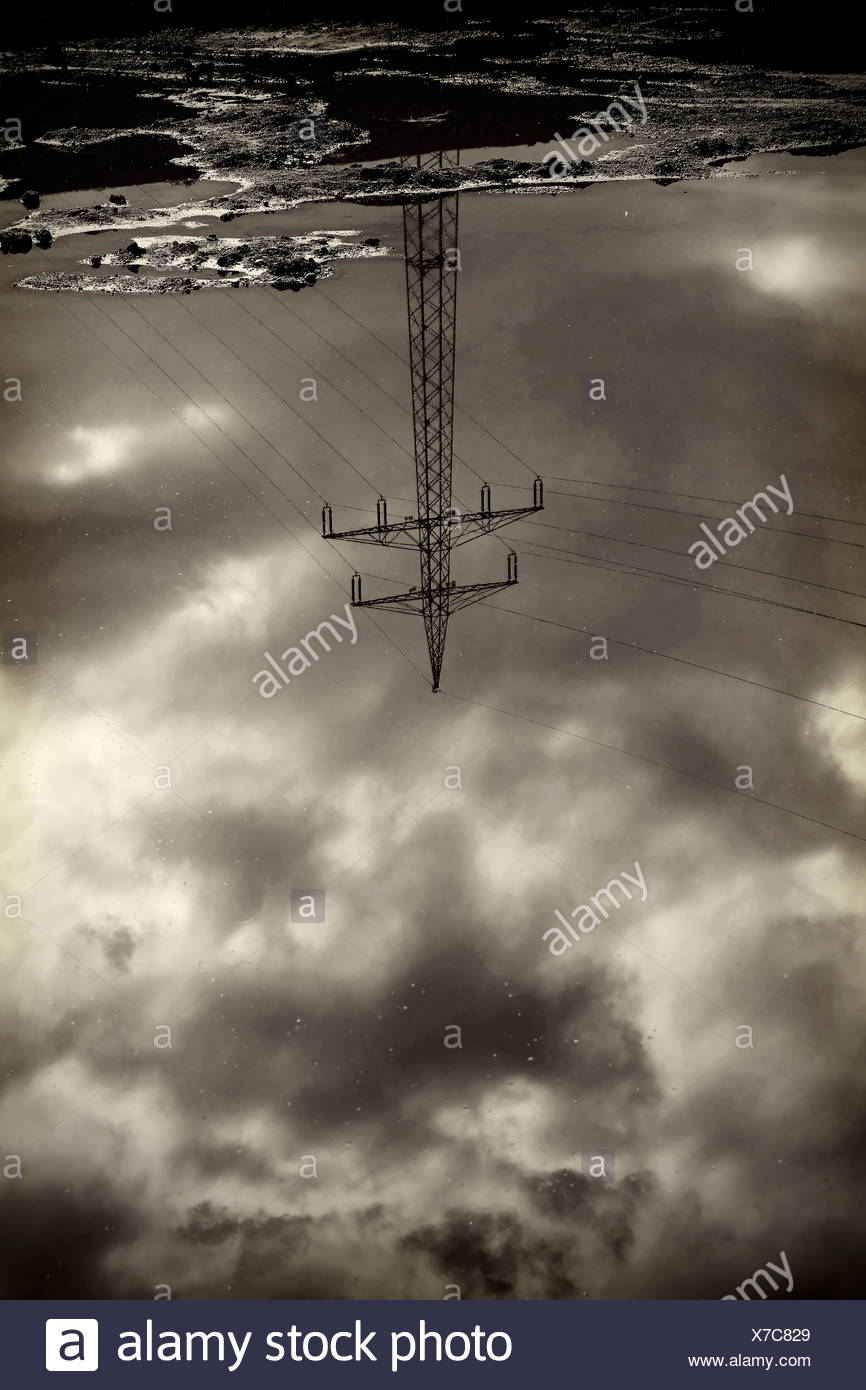 Power pylon reflecting in water surface - Stock Image