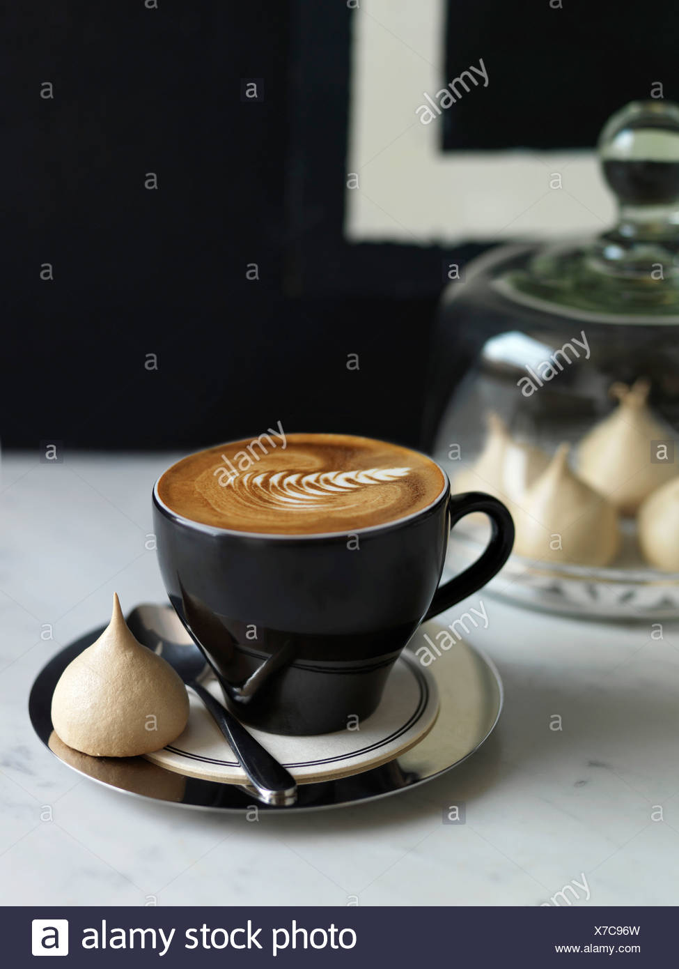 Cup of Cappuccino and a small meringue - Stock Image