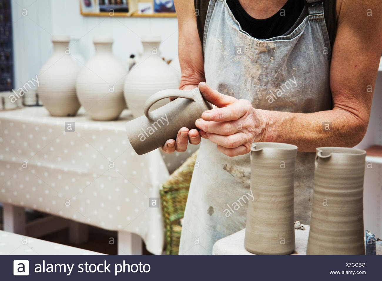 A potter handling a wet clay pot, smoothing the bottom and preparing it for kiln firing. - Stock Image