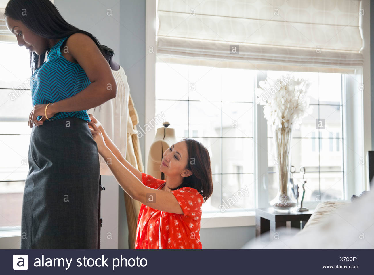 Female seamstress doing alterations in home studio - Stock Image