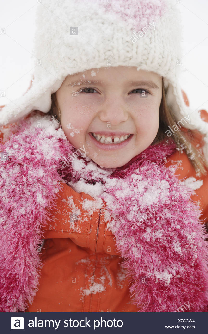 Girls winters cap scarf winter-clothing snow smiles gaze camera portrait child 4-6 years childhood freely winter-fun season - Stock Image