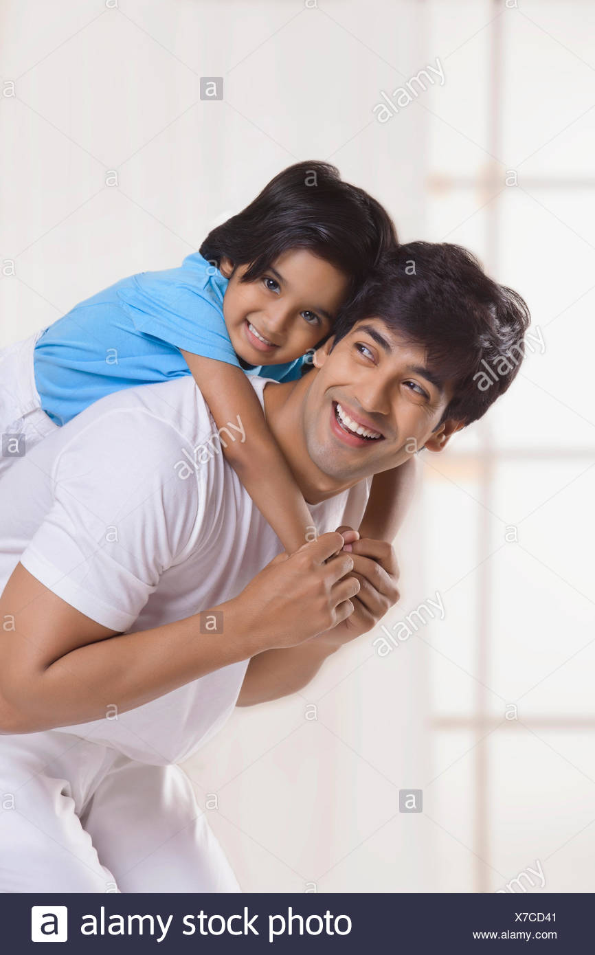 Portrait of father and son smiling - Stock Image