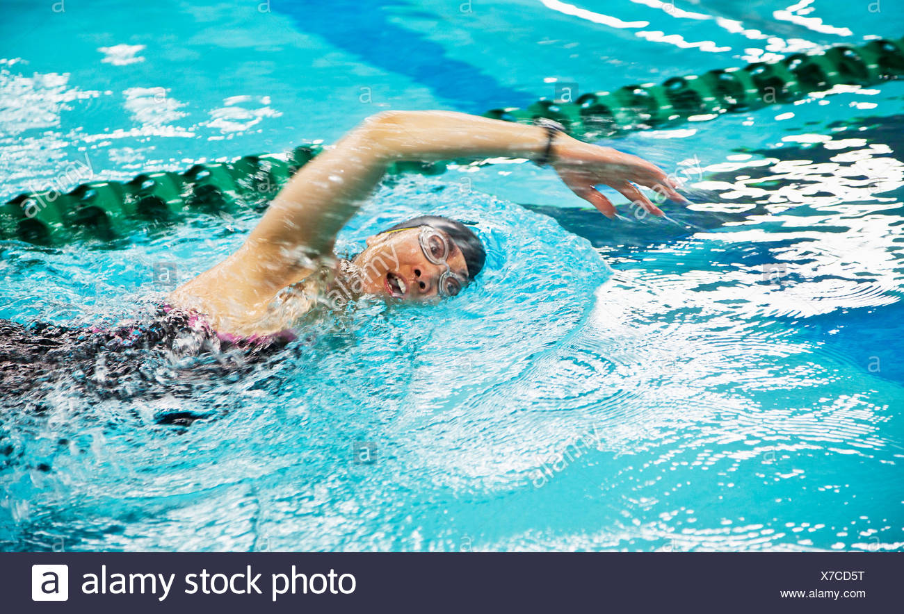 a woman wearing a cap and goggles swims the front stroke in a lane at a swimming pool; edmonton, alberta, canada Stock Photo