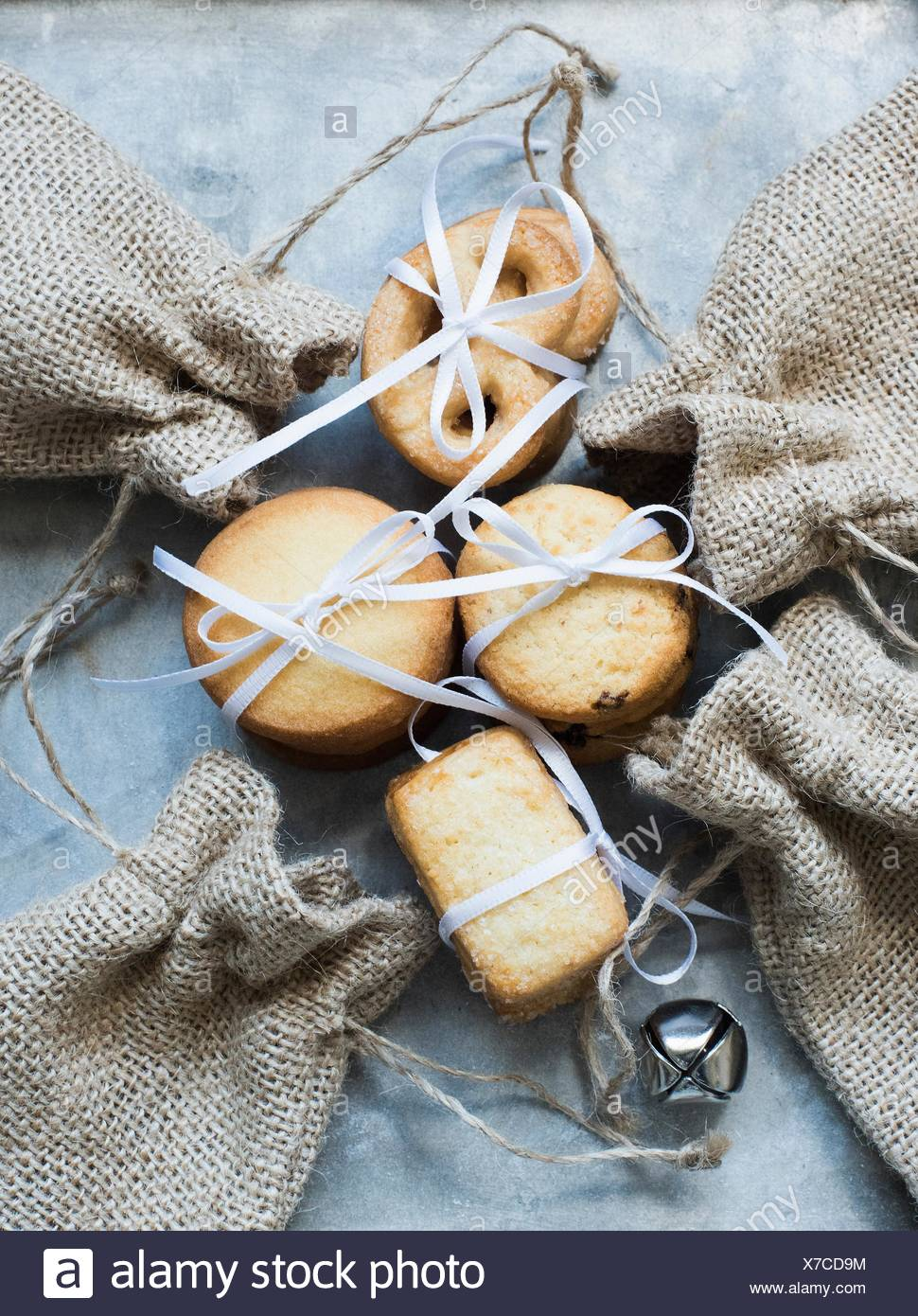 Overhead view of shortbread cookies tied with white ribbon and burlap bags - Stock Image