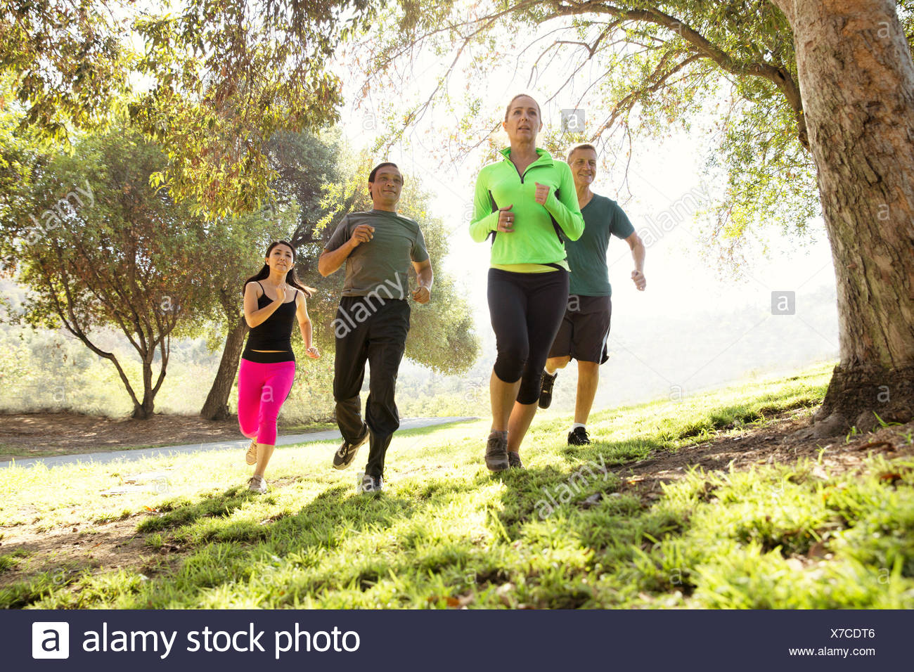 Four mature men and women running in park - Stock Image