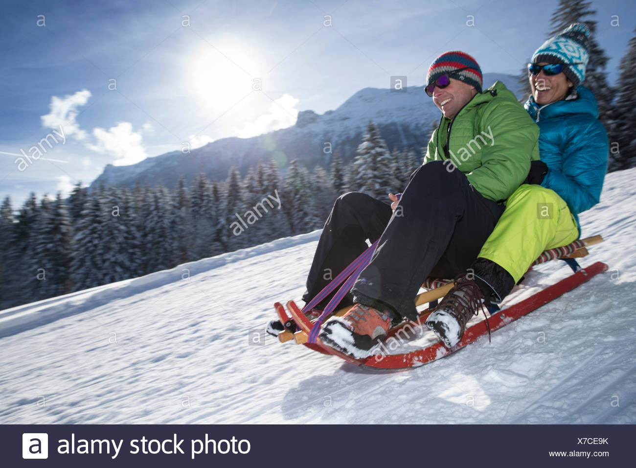 Germany, Bavaria, Inzell, couple having fun on a sledge in snow-covered landscape Stock Photo