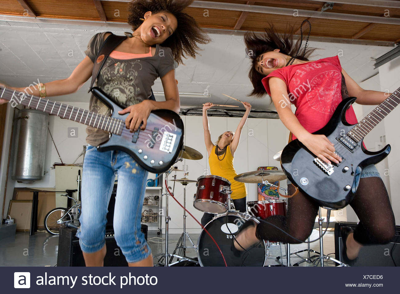 Three teenage girls  in garage band, two girls playing electric guitar in foreground - Stock Image
