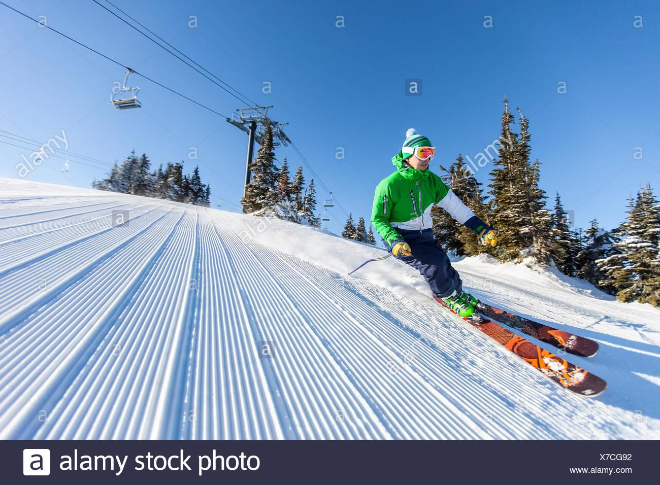 Mature man on ski slope under blue sky - Stock Image