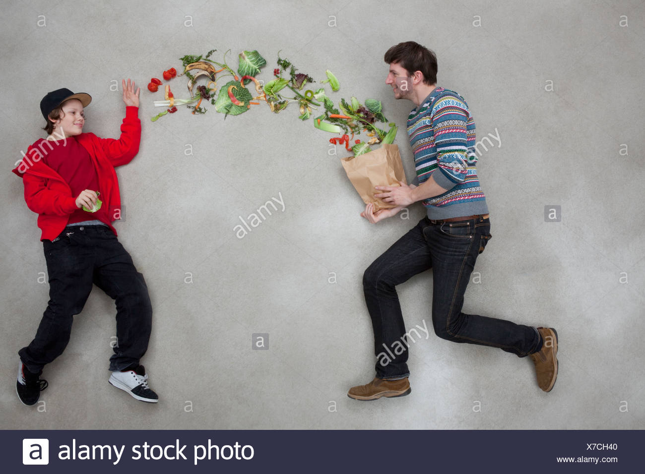 Man and boy balancing vegetables - Stock Image