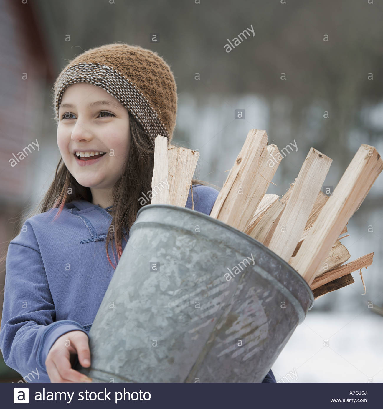 An organic farm in winter in New York State USA A girl carrying a bucket full of kindling and firewood - Stock Image