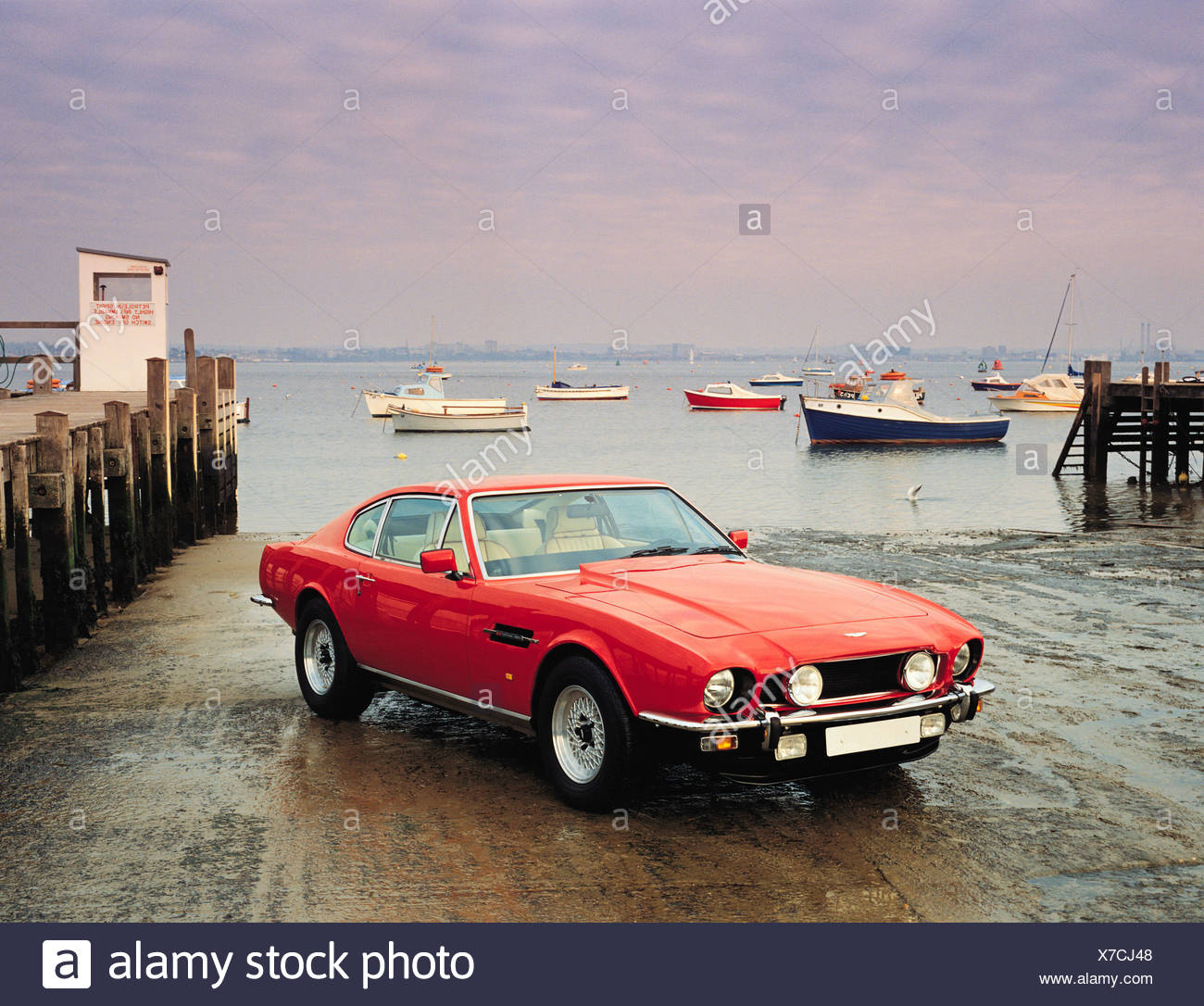 Red Aston Martin Dbs Sports Car On Harbour Slipway With Boats In Background British 1980 S Classic Motor Vehicle Stock Photo Alamy